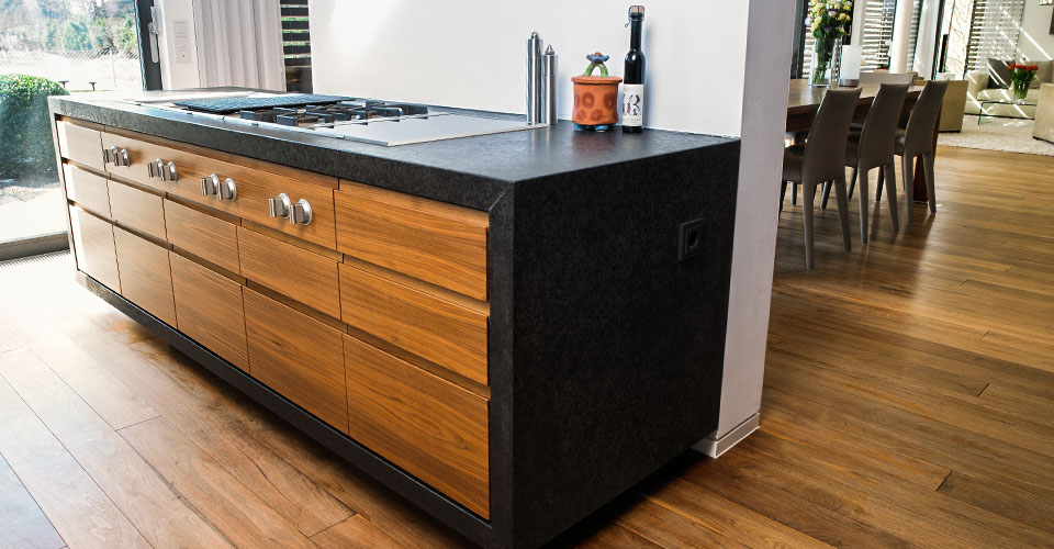 schwebender Küchenblock in Granit schwarzem Stein und Küchenfronten Nußbaum mit Griffmulden