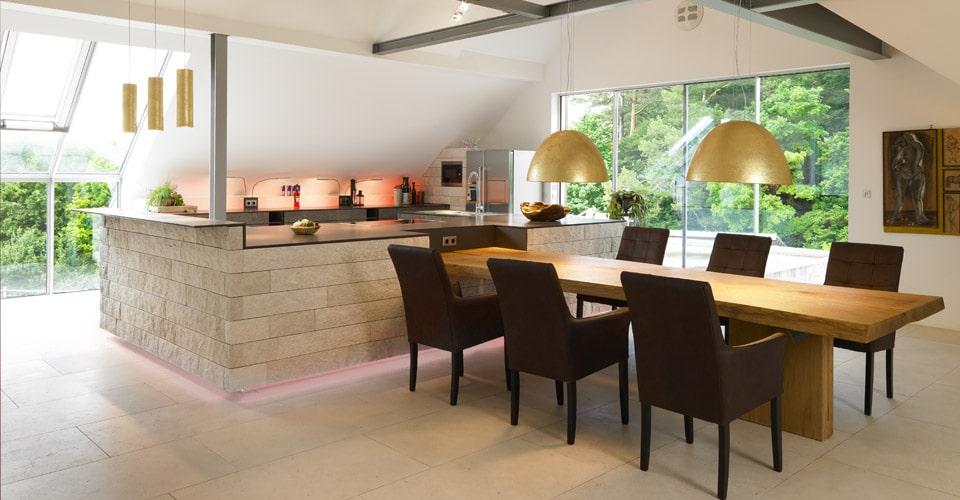 Küche mit integriertem Baum-Esstisch in Eiche massiv goldene Deckenlampen und Küchenfront mit echtem Steinmosaik